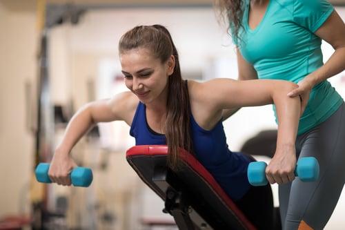 bigstock-Personal-Trainer-Helping-Prett-257358871
